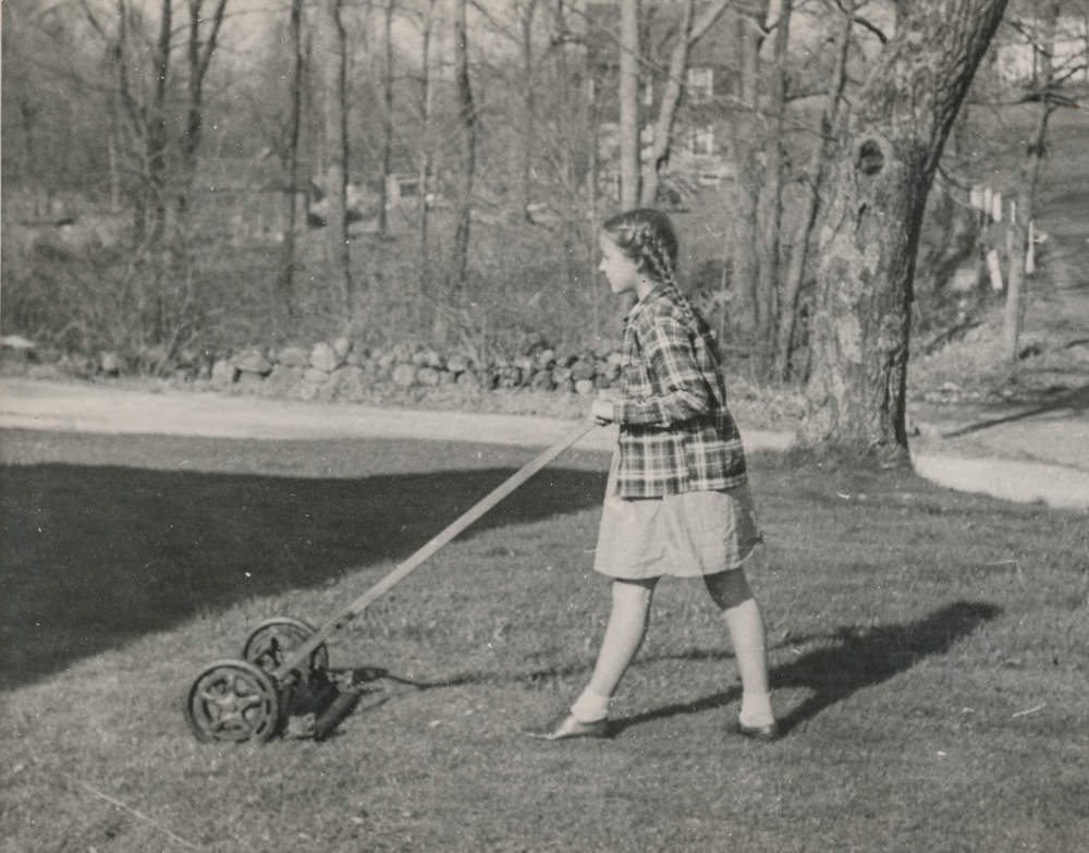 """""""June Lockton helping her father mow the lawn."""" Undated"""